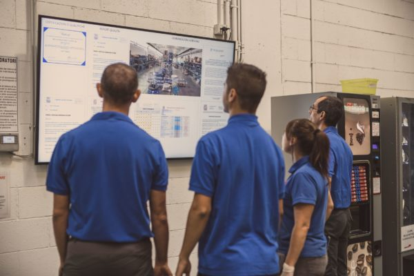 photo of people looking at a screen in a factory